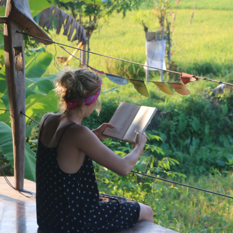 Woman reads book in Guatemala at a 200 hour yoga teacher training retreat